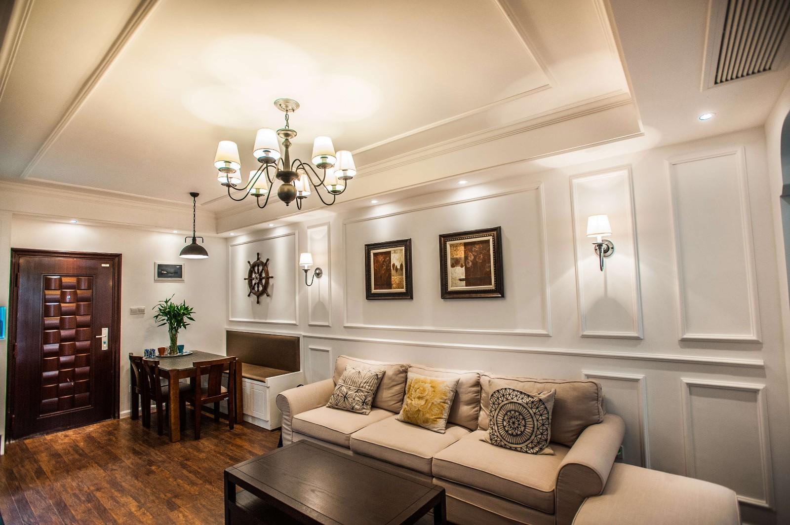 沙发背景墙采用石膏线条配合壁灯装饰画使画面丰富更有层次.
