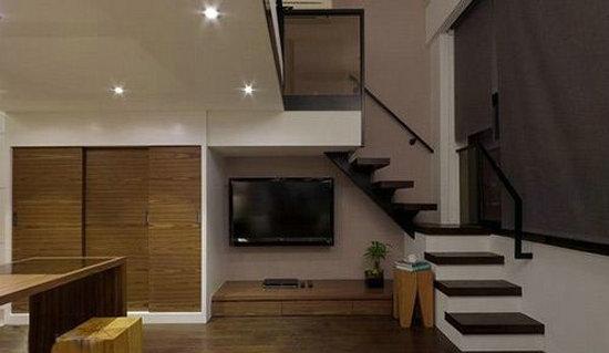 小复式公寓装修可以选择旋转角度较小的楼梯设计,咖啡色实木楼梯底下